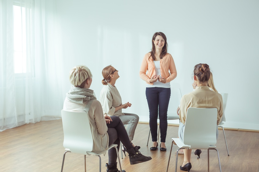 Happy young woman standing in front of support group